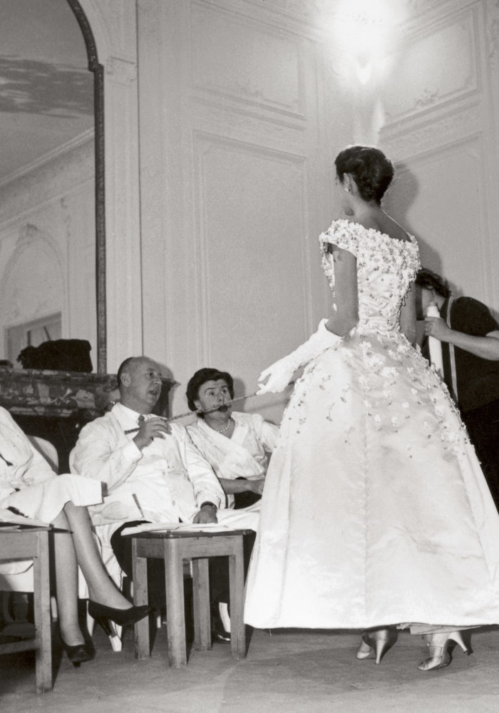 Christian Dior working with Mitzah Bricard (left) and Marguerite Carré (right) on the Première soirée dress, autumn−winter 1955 haute couture collection. Dior Heritage collection, Paris © Christian Dior / Photo: Bellini